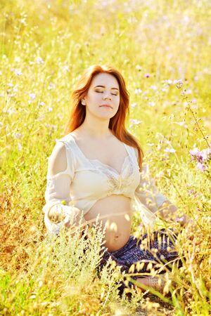pregnant woman doing meditation in wheat field Archivio Fotografico - 148970512