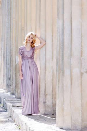 beautiful girl wearing long dress near the columns