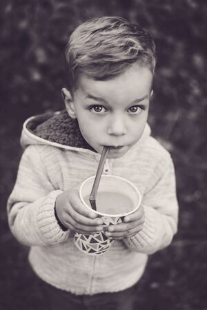 Little child walking in the forest and drinking hot cocoa at autumn day Archivio Fotografico