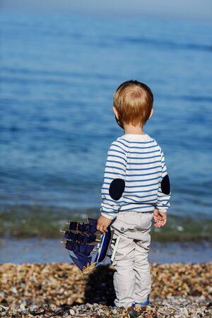 little boy standing near the sea and holding ship