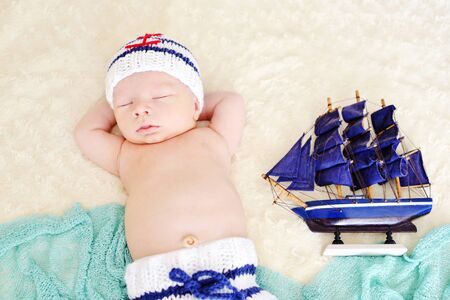 newborn boy is wearing a sailor coscume
