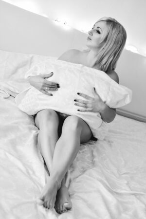 sensual blonde woman laying on the bed in bedroom Archivio Fotografico