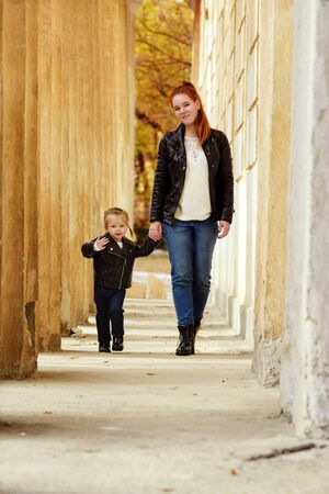 mother and toddler daughter walking on the street in fall Archivio Fotografico