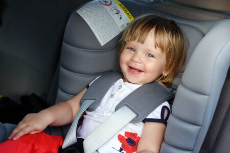a cute toddler girl in car seat