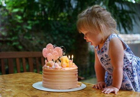 second birthday of sweet little girl with candle and cake