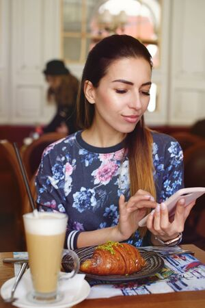 beautiful woman drinking coffee with croissant and using smart phone.