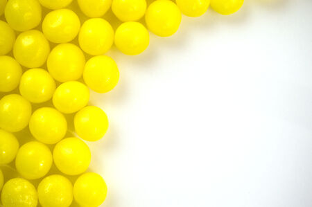 Yellow candy balls on blank white board