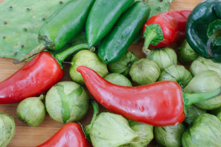 Healthy assortment of hot peppers, tomatillos, and cactus photo