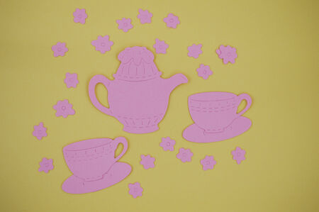 Paper cut out of pink teapot with cups and saucers photo