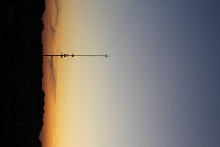 A radio tower over short soybean plants growing in an agricultural field under a colorful sky.