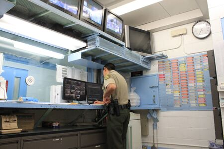Nogales, Ariz.  US - March 8, 2011: Santa Cruz County Sheriffs Office depuites work in the old, outdated jails dispatch center just before the opening of departments new facility. Editorial