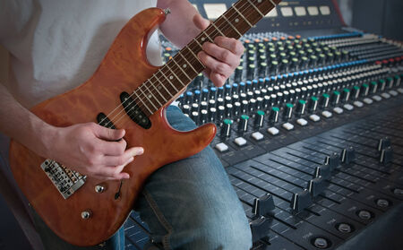 Man playing electric guitar in studio