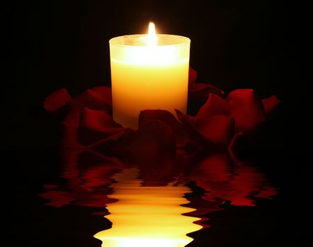 candle surrounded by rose petals with dreamy reflection photo