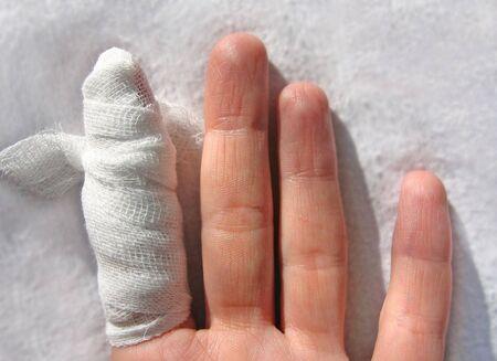 bandaged: finger by bandaged medical bandage , on white fabrics Stock Photo