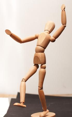 Wooden manequin figure dancing on papers photo