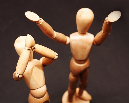 Two wooden figures standing and clapping in hands photo