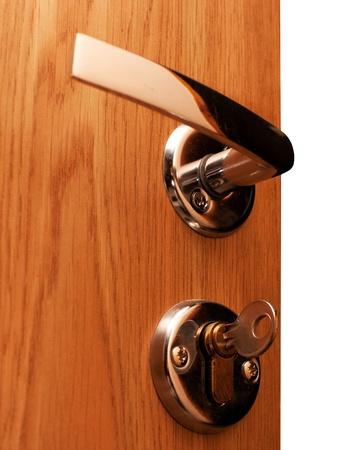 Wooden doorway with shiny keyhole, key inserted