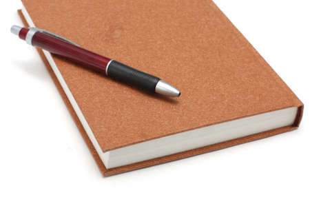 Brown diary lying on white surface with pen isolated on white background photo