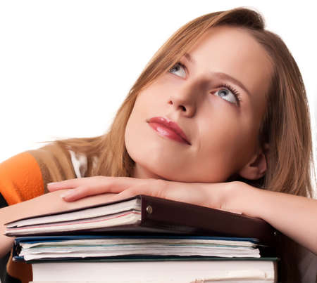 Young girl student with pile of books dreaming on white background Stock Photo