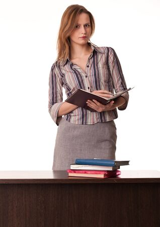 Confident woman teacher holding textbook standing behind the desk on white background photo