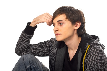 looking away from camera: Young man sitting and thinking looking away from camera