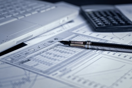Various financial charts on the table with laptop, calculator and pen