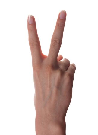 Woman hand shows victory gesture on white background photo