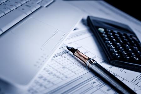 crisis economica: Varios gr�ficos financieros sobre la mesa con el port�til, calculadora y pluma Foto de archivo