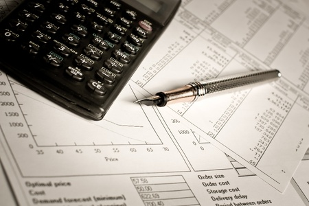 Financial charts and tables lying on the table with calculator and pen