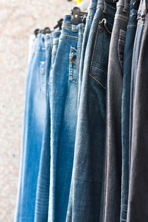 bluejeans: Blue and black jeans on hangers for sale