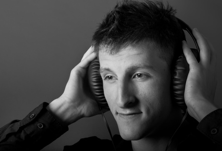 Young male person listening to music with headphones photo
