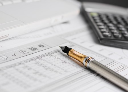 Accounting in process with calculator, pen and financial charts Stock Photo
