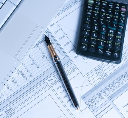 contabilidad financiera cuentas: Contabilidad en proceso con gráficos financieros, pluma y calculadora