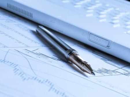contabilidad financiera cuentas: Contabilidad con la pluma y el ordenador port�til sobre la mesa Foto de archivo