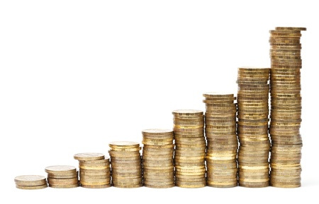 pile of money: Golden coins stacks forming graph on white background Stock Photo