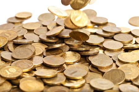 Shiny golden coins falling on white background photo