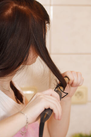 Young woman makes curlier by curling iron photo