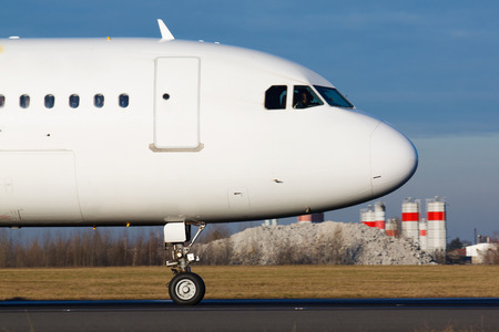 Detail of white plane nose during taxi on taxiway Фото со стока