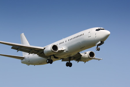 White clean plane landing in sunny day