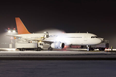 White plane with red tail during de-icing in winter photo