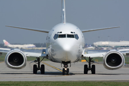 Taxiing white plane in hot and sunny day