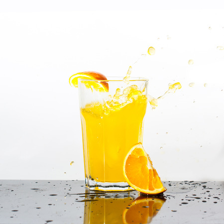 Splashing orange drink with falling orange on white background Фото со стока