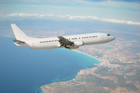 White plane in flight with island Mallorca in background photo
