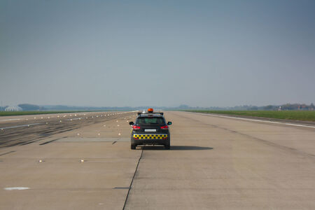 Car with orange light controlling runway at the airport Standard-Bild
