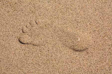 Mark of foot in the sand at the sea photo