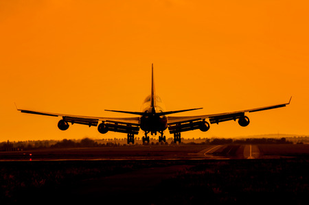 airplane take off: Huge plane with four engines landing in sunset