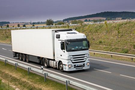 camion: Cami�n blanco pesado con remolque en carretera nueva Foto de archivo