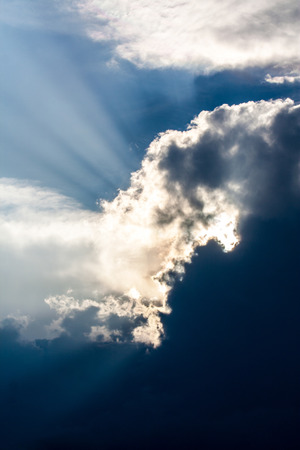 dramatic clouds: Sun is shining behind very dark clouds