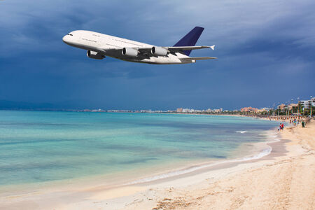 Huge plane flying over the beach during your vacation photo