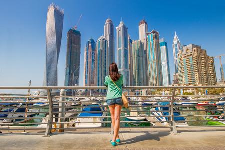 Jonge vrouw op zoek op wolkenkrabbers in Dubai Marina
